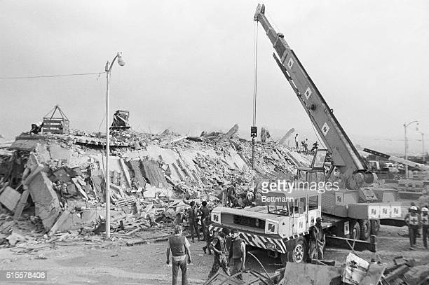 Workers use a large crane to move the rubble of a US marine barracks in Beirut, Lebanon which collapsed after a truck filled with explosives crashed...
