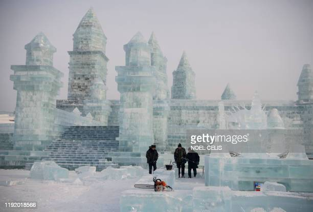 Workers use a shovels to clear some snow before tourists arrive at the Harbin International Ice and Snow Festival in Harbin in China's northeast...