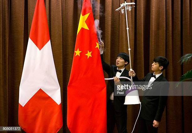 Workers use a steam iron on a Chinese flag before a bilateral meeting between Chinese Foreign Minister Wang Yi and Swiss Foreign Minister Didier...
