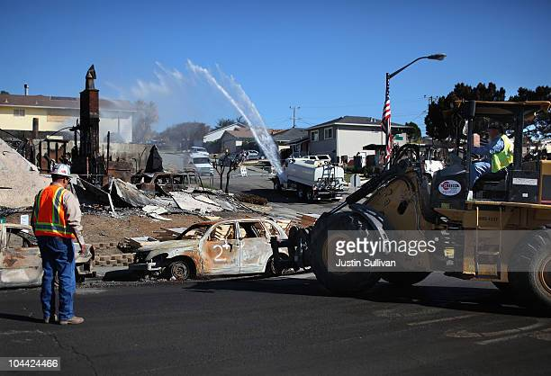 Workers use a tractor to move the shell of a car that sits in front of a burned home near the epicenter of the gas line explosion that devastated a...