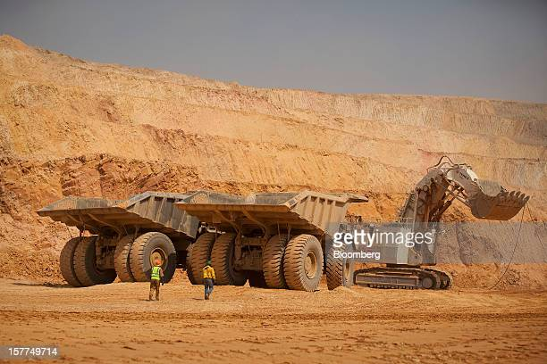 Workers use Caterpillar Inc mining trucks and a Terex Corp mining excavator to remove ore from the open pit during excavations at Katanga Mining...