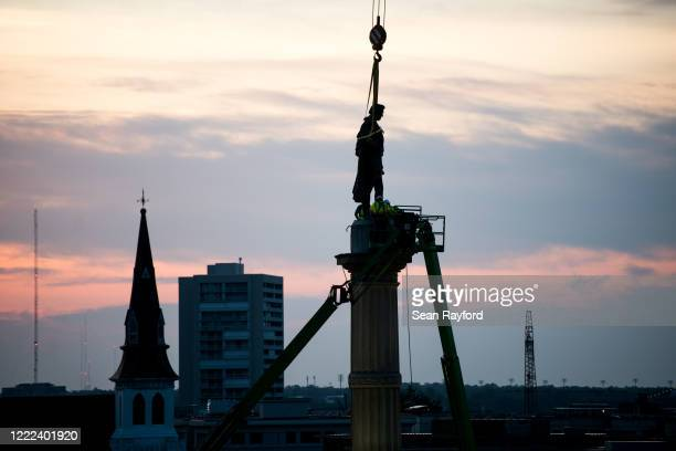 Workers use cherry pickers to access the statue of John C Calhoun atop the monument in his honor at Marion Square on June 24 2020 in Charleston South...