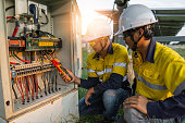 Workers use clamp meter to measure the current of electrical wires produced from solar energy for confirm to normal current