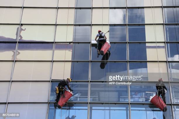 Workers use climbing rigging sytems as they apply window size portions of an advertizing banner on the CNIT building in the La Defense business...