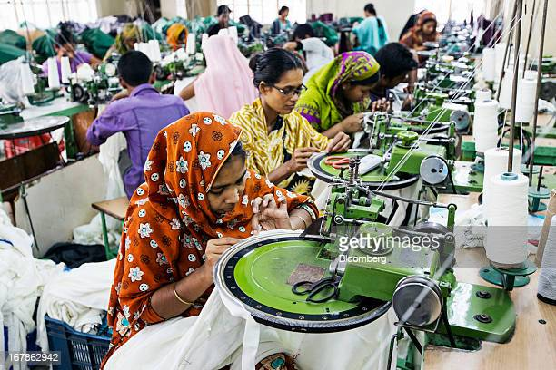 Workers use dial linking machines on the production line of the Vintage Apparels Ltd garment factory in Dhaka Bangladesh on Monday April 29 2013...