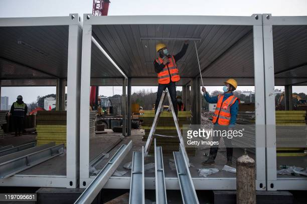 Workers use electric drills to install lights at Huoshenshan hospital as new hospitals are built to tackle the coronavirus on January 28 2020 in...