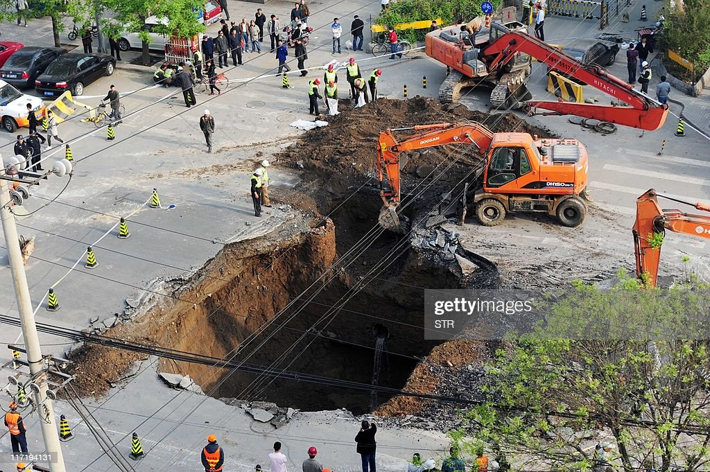 Workers use excavators to fill in a sink : News Photo