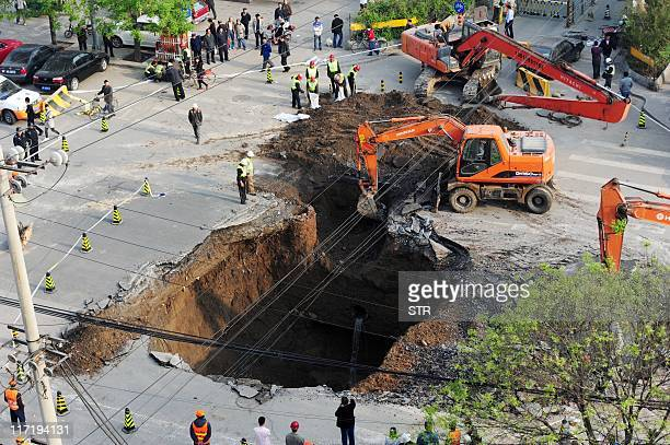 Workers use excavators to fill in a sinkhole which occured overnight on Shiliuzhuang road in Beijing on April 26 2011 A section of the road collapsed...