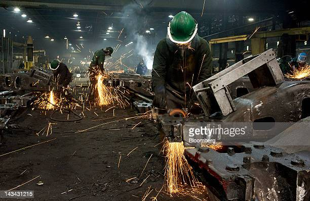 Workers use grinders to smooth down the welded joints for railroad suspension parts at the Columbus Castings facility in Columbus Ohio US on...