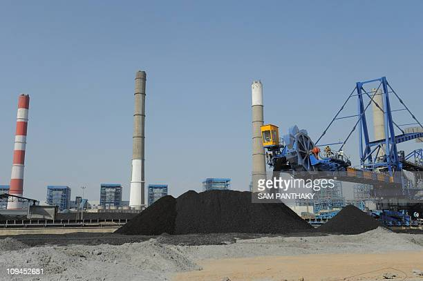 Workers use heavy machinery to sift through coal at the Adani Power company thermal power plant at Mundra some 400 kms from Ahmedabad on February 18...