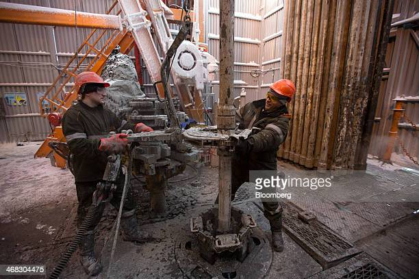 Workers use machinery to move drill sections on the drilling floor of the oil derrick in the Salym Petroleum Development oil fields near the Bazhenov...