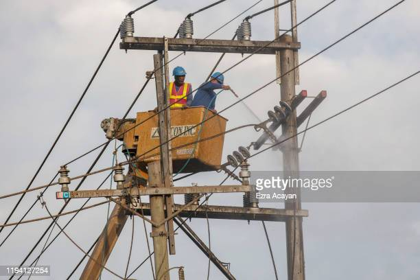 Workers use pressurised water to clean an electrical post covered in volcanic ash from Taal Volcano's eruption on January 17 2020 in Tagaytay city...