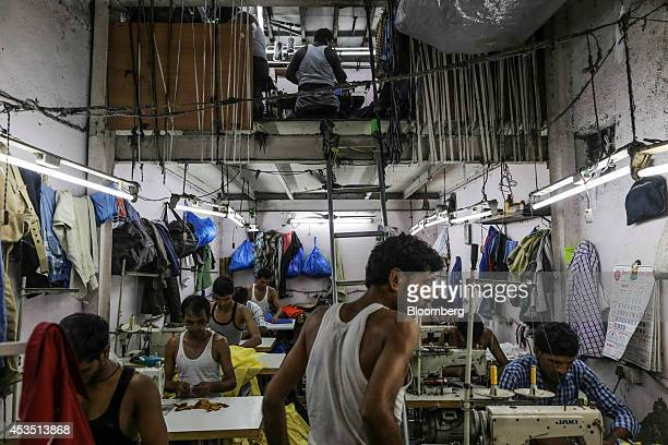 Workers use sewing machines at a garment workshop in the Dharavi slum area of Mumbai India on Monday Aug 11 2014 Almost a year after Reserve Bank of...