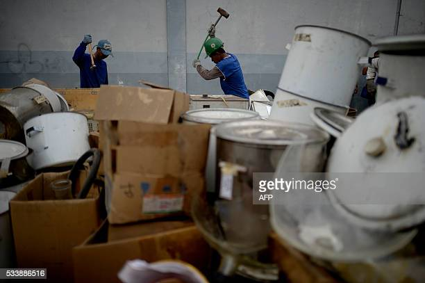 Workers use sledge hammer to destroy seized laboratory equipment used for the production of illegal drug methamphetamine hydrochloride headed by...