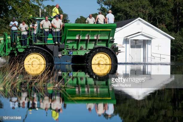 Workers uses farm machinery to navigate floodwaters from the Waccamaw River caused by Hurricane Florence on September 26, 2018 in Bucksport, South...