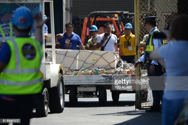 Workers using a cart pull the wooden casket containing the body of Filipina overseas worker Joanna Demafelis whose body was found inside a freezer in...