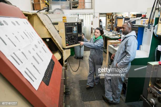 Workers using control panel in factory