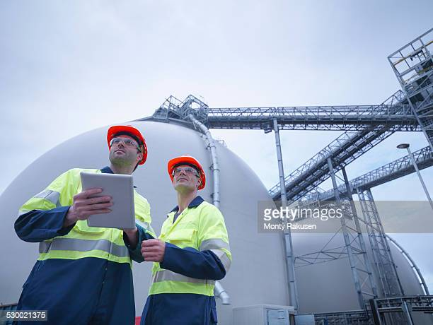 Workers using digital tablet at biomass facility, low angle view