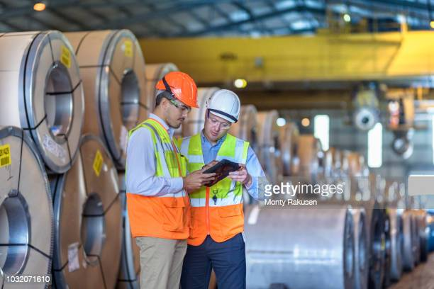 workers using digital tablet by rows of sheet steel in storage at port - monty rakusen stock photos and pictures
