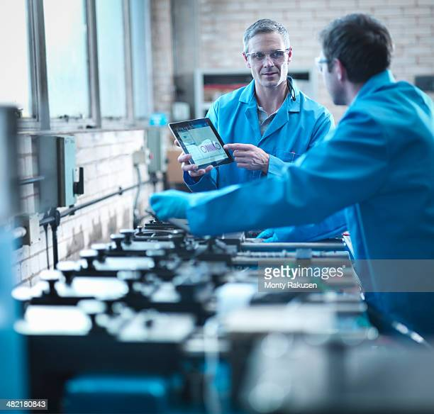 Workers using digital tablet for testing springs in laboratory