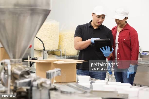 Workers using digital tablet in factory
