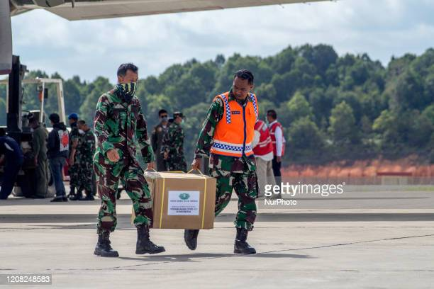 Workers using heavy equipment lift medical equipment to be used for Corona Special Hospital at Hang Nadim Airport in Batam, Riau Islands, , on March...