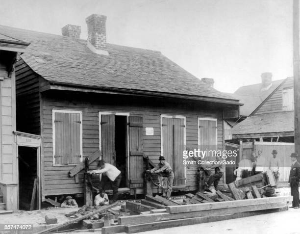 Workers using manual jacks to raise a small house off its foundation during a construction project 1914 Image courtesy CDC