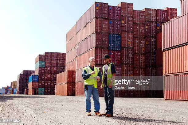 workers using tablet computer while discussing at commercial dock - dock worker stock photos and pictures