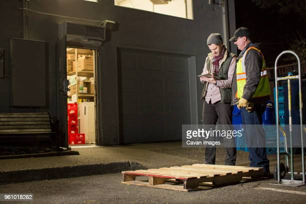workers using tablet computer while standing by warehouse at night - cavan images foto e immagini stock