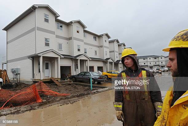 Workers view houses selling for around 450000 USD at a new property development in the oil sands rich boomtown of Fort McMurray in Alberta on October...