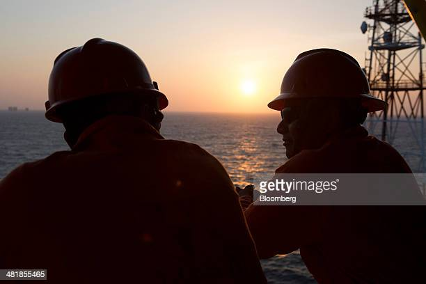 Workers wait in the heliport area during sunset at the Petroleos Mexicanos PolA Platform complex located on the continental shelf in the Gulf of...