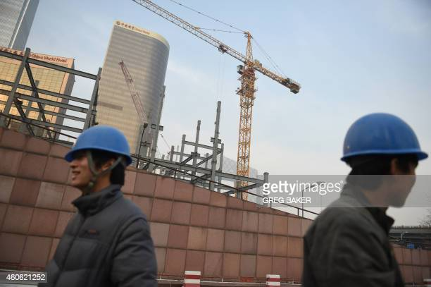 Workers wait near a construction site in Beijing on December 18 2014 Foreign investment into China accelerated in November government data showed...