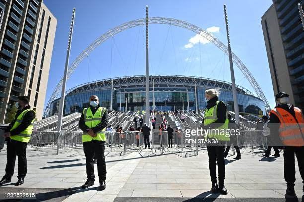Workers wait to admit fans to Wembley Stadium to watch the English League Cup final football match between Manchester City and Tottenham Hotspur, in...