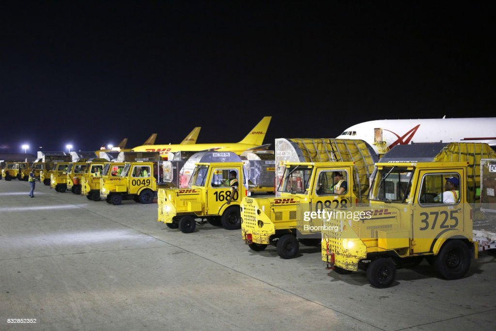 Workers wait to transport package containers at the DHL Worldwide Express hub of Cincinnati/Northern Kentucky International Airport in Hebron, Kentucky, U.S., on Wednesday, Aug. 16, 2017. The Deutsche Post AG, parent company to Worldwide Express, second-quarter operating profit jumped 12 percent as the German mail operator handled more express deliveries and won more business at its logistics unit. Photographer: Luke Sharrett/Bloomberg via Getty Images