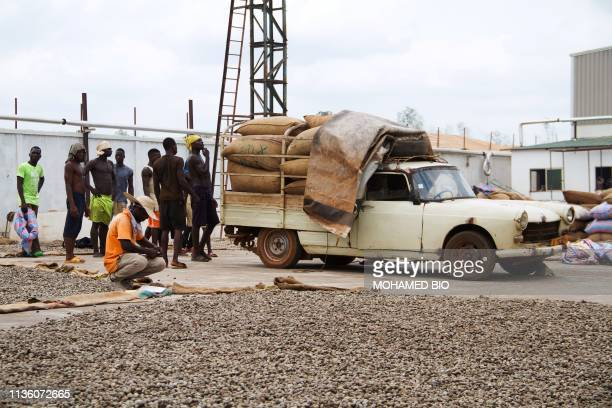 Workers wait to unload bags of cashew nuts from a truck for the drying process at the Fludor plant in Zogbodomey, some 110km north of Cotonou, on...