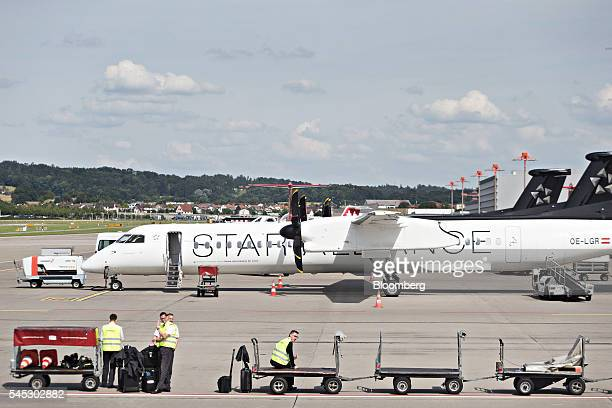 Workers wait to unload luggage from a passenger aircraft operated by Star Alliance at Zurich Airport operated by Flughafen Zuerich AG in Zurich...