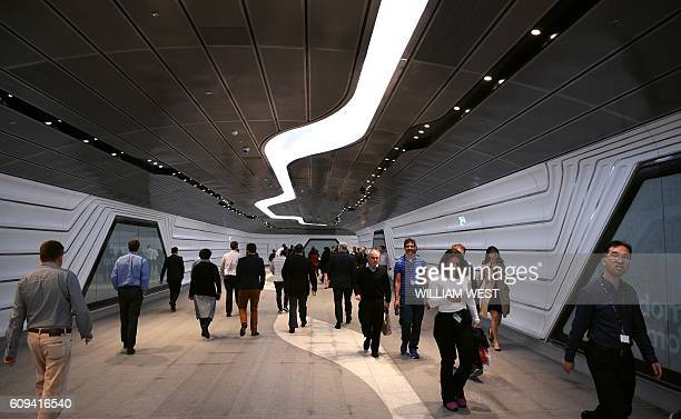Workers walk a new tunnel through the developing office and residental area of Barangaroo in Sydney's innercity on 21 September 2016 / AFP / WILLIAM...