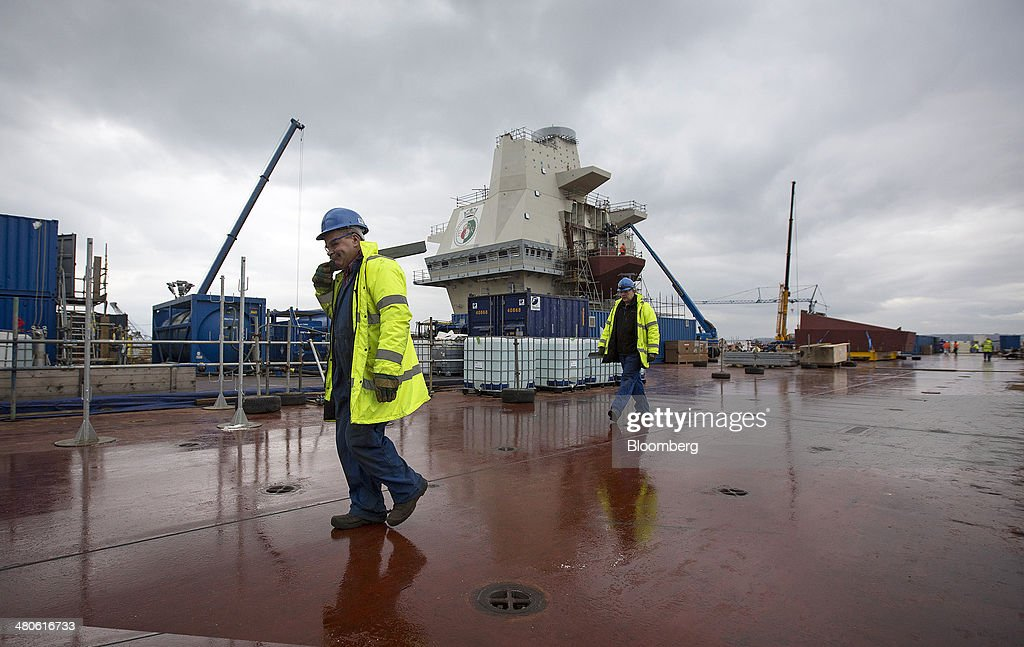 Workers walk across the flight deck of the Royal Navy's new Queen Elizabeth class aircraft carrier, manufactured by the Aircraft Carrier Alliance, a joint operation between BAE Systems, Thales SA and Babcock International Group Plc, at Babcock shipyard in Rosyth, U.K., on Tuesday, March 25, 2014. Construction of hull sections for the HMS Queen Elizabeth and HMS Prince of Wales aircraft carriers is being undertaken at BAE's Scotstoun and Govan yards on the River Clyde in Glasgow, with the ships due to be assembled at Babcock International Group's dockyard in Rosyth, near Edinburgh. Photographer: Simon Dawson/Bloomberg via Getty Images