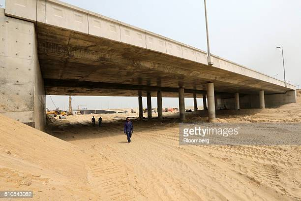 Workers walk along a partially excavated roadway beneath a new highway bridge at the Eko Atlantic city site, developed by Eko Atlantic, near Victoria...