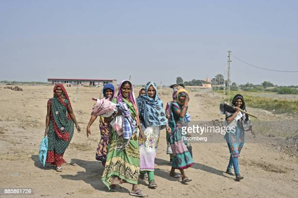 Workers walk along a road after their shift on a project site for a 920squarekilometer industrial area located on the DelhiMumbai Industrial Corridor...