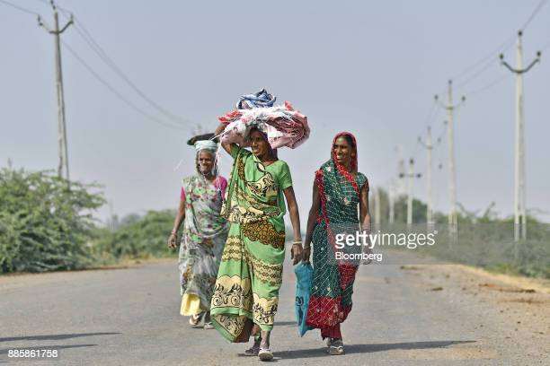 Workers walk along a road after their shift on the project site for a 920squarekilometer industrial area located on the DelhiMumbai Industrial...