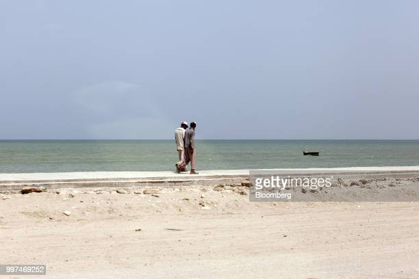 Workers walk along a sidewalk on Marine Drive in Gwadar Balochistan Pakistan on Tuesday July 4 2018 What used to be a small fishing town on the...