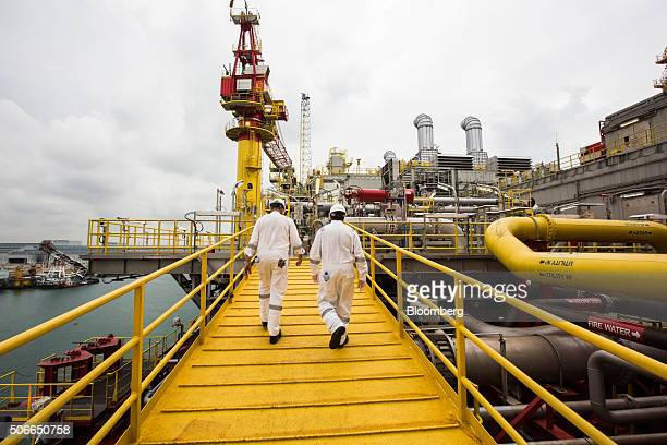 Workers walk along an elevated walkway on the Tullow Oil Plc Prof John Evans Atta Mills Floating Production Storage and Offloading vessel docked at...