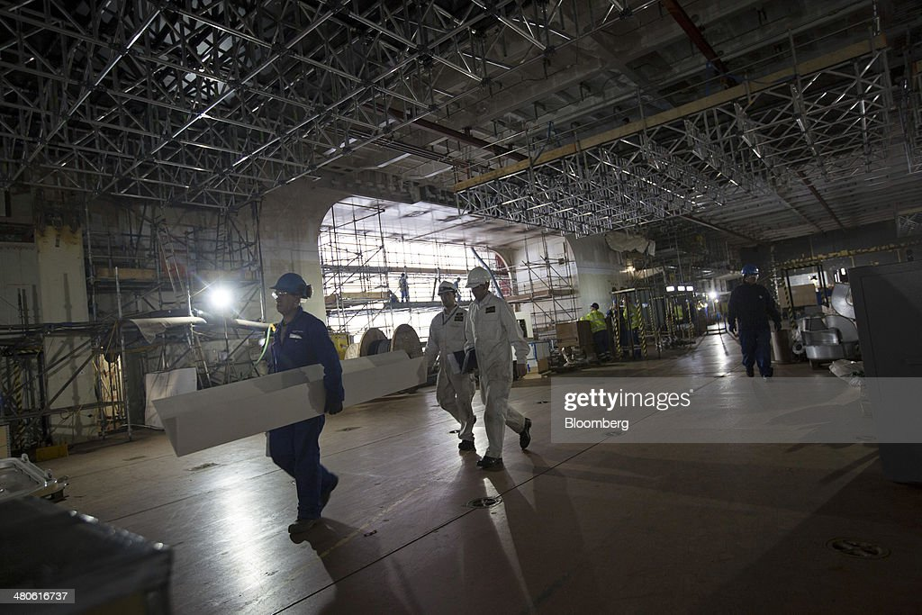 Workers walk along an inside deck onboard the Royal Navy's new Queen Elizabeth class aircraft carrier, manufactured by the Aircraft Carrier Alliance, a joint operation between BAE Systems, Thales SA and Babcock International Group Plc, at Babcock shipyard in Rosyth, U.K., on Tuesday, March 25, 2014. Construction of hull sections for the HMS Queen Elizabeth and HMS Prince of Wales aircraft carriers is being undertaken at BAE's Scotstoun and Govan yards on the River Clyde in Glasgow, with the ships due to be assembled at Babcock International Group's dockyard in Rosyth, near Edinburgh. Photographer: Simon Dawson/Bloomberg via Getty Images