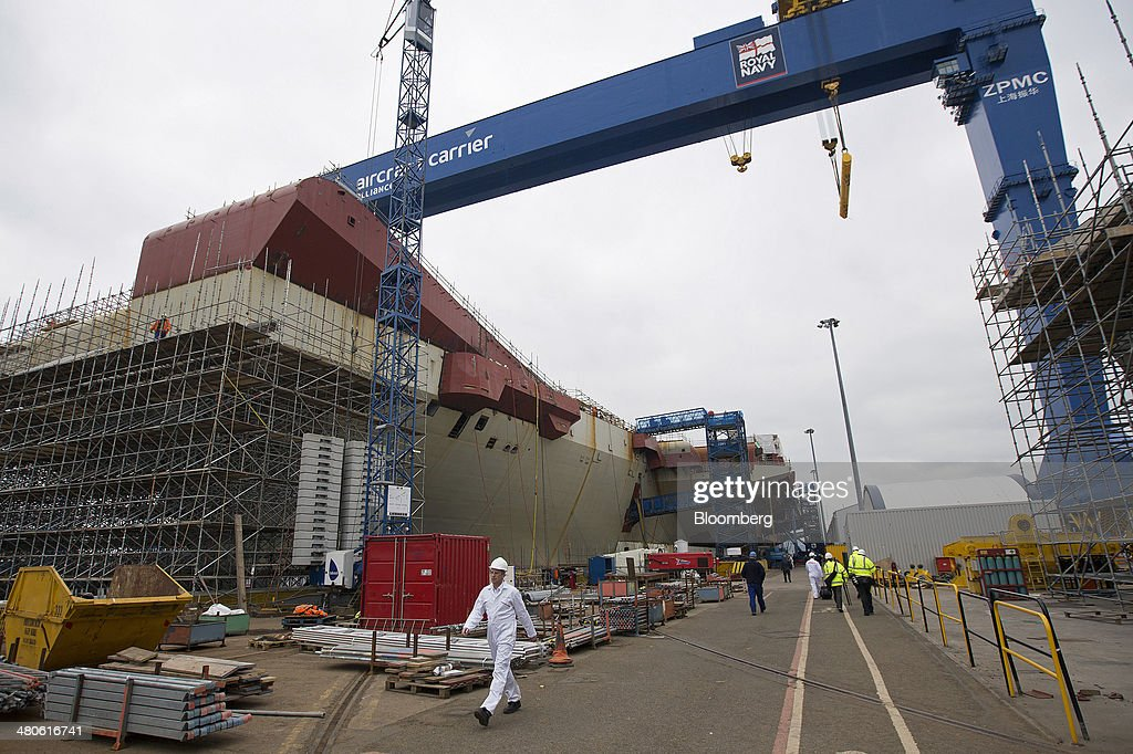 Workers walk along the dockside near the Royal Navy's new Queen Elizabeth class aircraft carrier, manufactured by the Aircraft Carrier Alliance, a joint operation between BAE Systems, Thales SA and Babcock International Group Plc, at Babcock shipyard in Rosyth, U.K., on Tuesday, March 25, 2014. Construction of hull sections for the HMS Queen Elizabeth and HMS Prince of Wales aircraft carriers is being undertaken at BAE's Scotstoun and Govan yards on the River Clyde in Glasgow, with the ships due to be assembled at Babcock International Group's dockyard in Rosyth, near Edinburgh. Photographer: Simon Dawson/Bloomberg via Getty Images