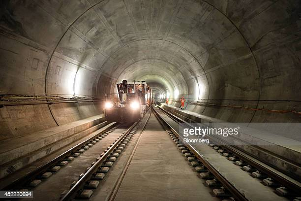Workers walk alongside a support freight train inside the east section of the Gotthard Base Tunnel in Faido Switzerland on Tuesday July 15 2014...