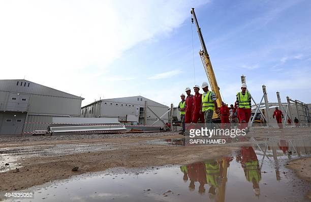 Workers walk at the new living camp for German soldiers in Arbil the capital of the autonomous Kurdish region of northern Iraq on October 26 2015...