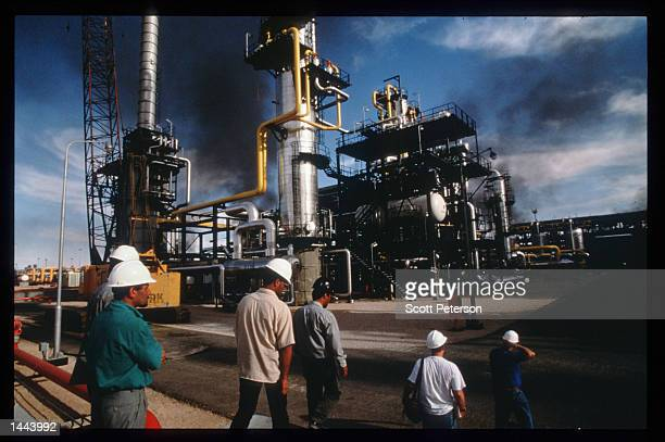 Workers walk at the southern complex refinery June 15 1997 in Hassi Messaoud Algeria The recent completion of a multibillion dollar oil refinery by...