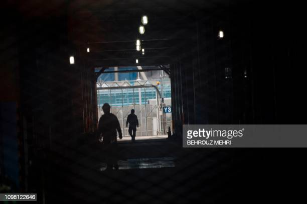 Workers walk at the under construction Ariake Arena venue for volleyball at the Tokyo 2020 Olympic Games and wheelchair basketball in the Paralympic...