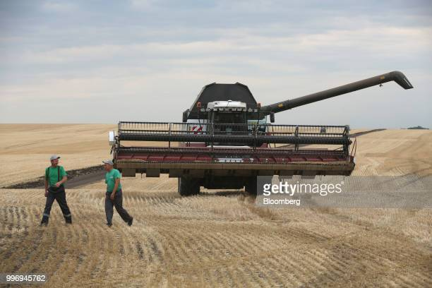Workers walk in a wheat field as a Torum combine harvester manufactured by Rostselmash OJSC stands beyond during the summer harvest on a farm...